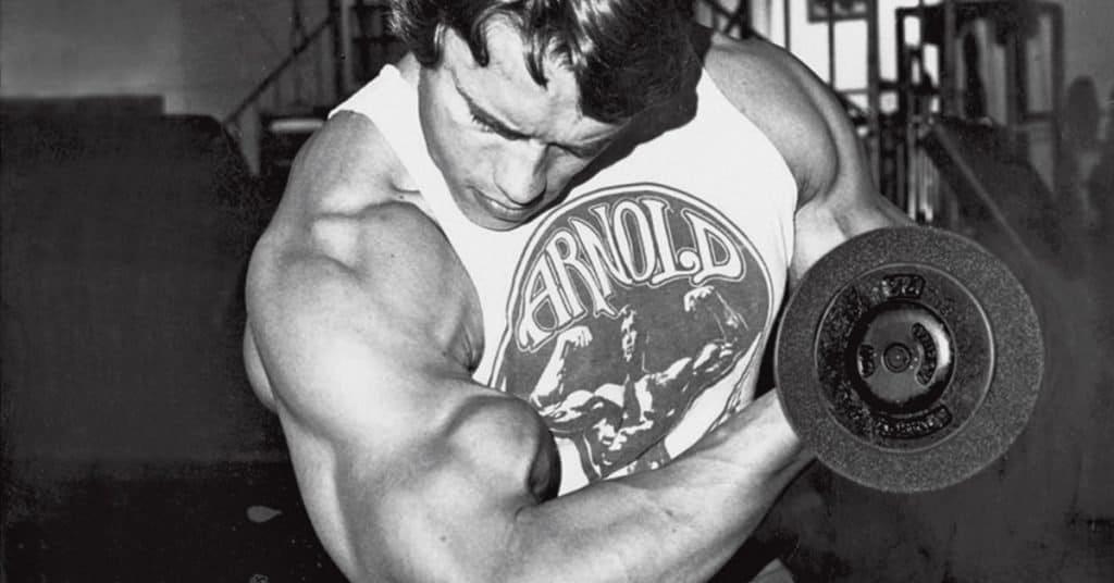 Arnold haciendo curl de bíceps, como aumentar el tamaño de tus brazos